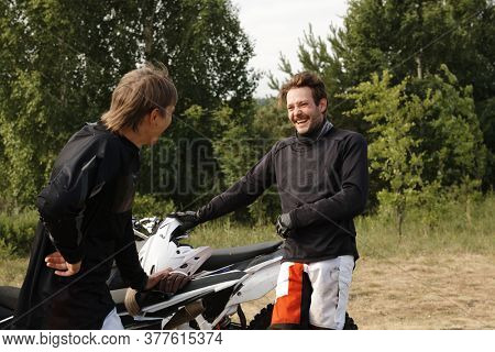 Positive young bikers holding motorcycles while chatting and laughing after race in forest