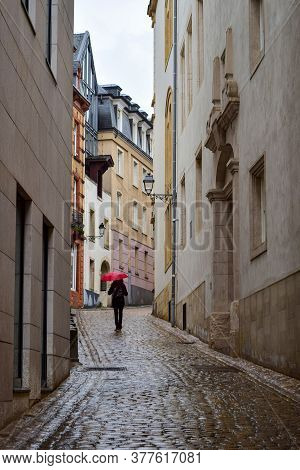 A Figure Walking Under An Umbrella On The Wet Cobblestones Among The Houses. Luxembourg City. Luxemb