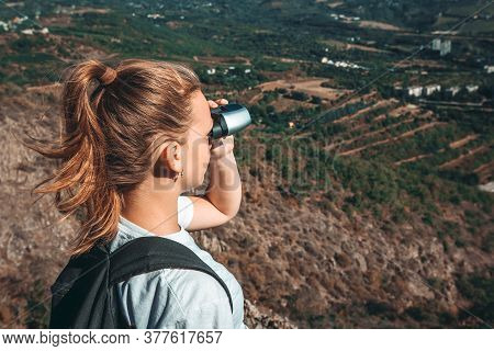 Hiker Girl With Backpack Looking In Binoculars Enjoying Spectacular View Of Valley On Mountain Top.