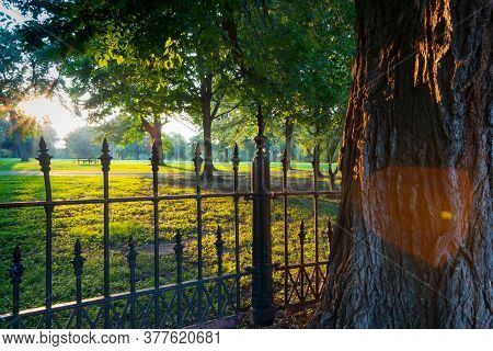 Long Shadows Through Wrought Iron Fence Surrounding La Fayette Park With Lens Flare  Effect At Sunse