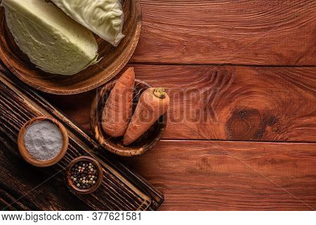 Pieces Of Cabbage, Unpeeled Carrots, Pepper And Salt On Wooden Surfaces And In Plates. Table Is Tone