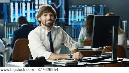 Portrait Of Male Stock Trader Operating At Her Workstation Using Computer And Looking At Camera On B