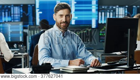Male Stock Trader Working At Stock Exchange Office And Looking At Camera On Background Of His Busine