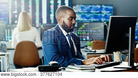 African American Male Stock Trader Working At Stock Exchange Office Using Computer On Background Of