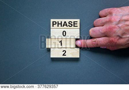 Wooden Blocks Form The Words 'phase, 0, 1, 2' On Blue Background. Male Hand. Beautiful Background. B