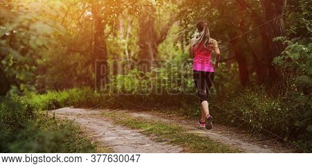 Young Fitness Woman Running In The Morning Forest Trail. Healthy Fit Living.