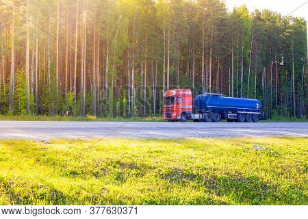 Blue Barrel Truck With Dangerous Cargo Is Parked On The Side Of A Forest Road, Transportation And Sa