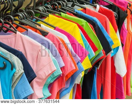 A Lot Of New T-shirts On Hangers In The Stores Showroom. Training Form On Hangers On The Shop Window