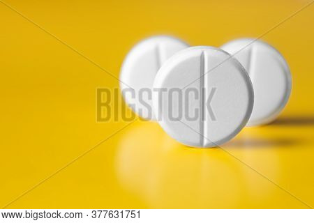 Three Large White Pill On A Yellow Background. Selective Focus