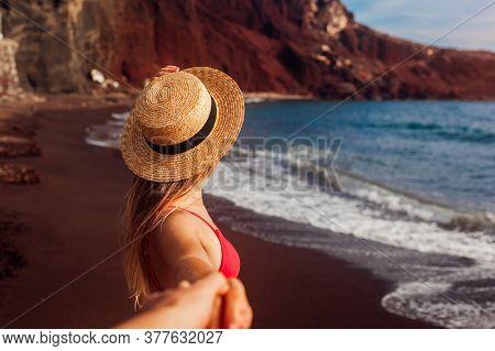 Follow Me. Sexy Woman In Bikini Relaxing On Red Beach In Santorini, Greece. Girl Holds Hand Of Man E