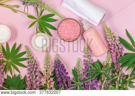 Spa Product Composition With Lupine Flowers, Towel And Cosmetic On A Pink Background.