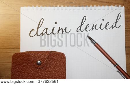 Claim Denied Words On Copybook Page, A Pen And Leather Wallet On Wooden Table. Business Sponsorship