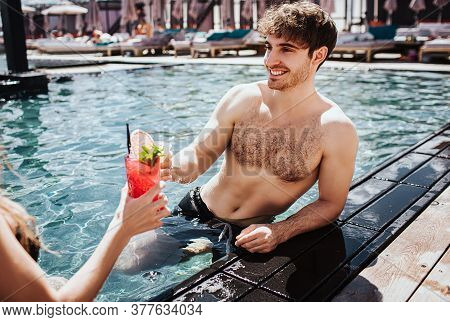 Young Hot Couple Resting At Swimpool. Sexy Guy In Water Holding Cocktails In Hand And Cheering With