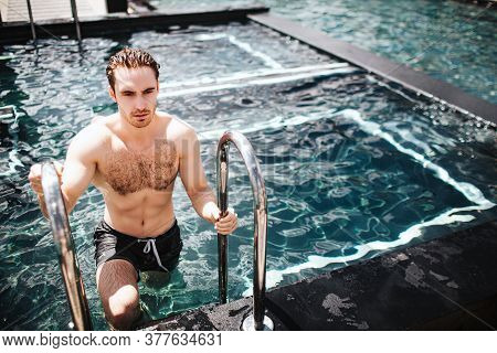 Young Hot Man Resting At Swimpool. Picture Of Man Walking Out Of Water Alone After Swimming. Enjoy H