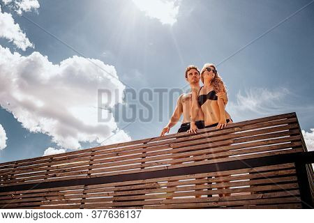 Young Hot Couple Resting Together. Slim Well-built Man And Woman In Swim Suits Stand At Edge Under S