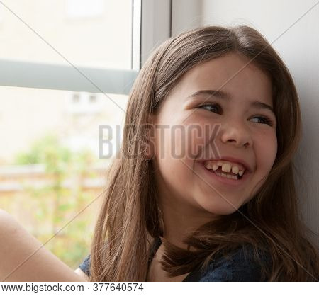 A Portrait Of A 7 Year Old Girl Sat On A Windowsill Of Mixed Race, Caucasian And Hispanic, Taken In