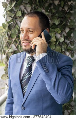 Handsome Man In A Suit And Tie, Is Talking On The Phone