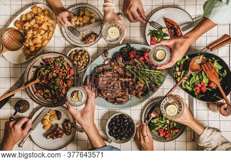 People Feasting At Barbeque Party With Meat, Salads, Lemon Water