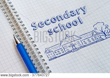 Notebook With A Spiral In A Cage And Blue Pen On It. On The Left Page Drawn The School And Lettering