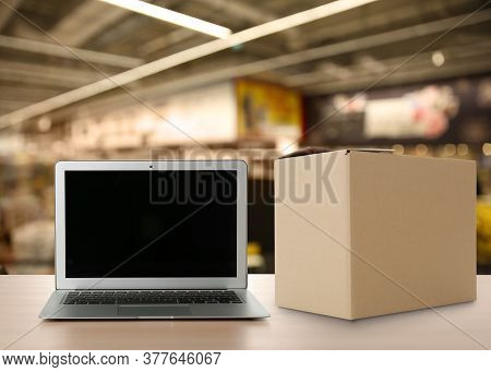 Online Selling. Laptop And Parcel On Table In Store
