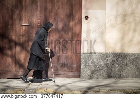 Sombor, Serbia - March 19, 2016: Old Woman Wearing A Erbiantraditional Back Outfit Walking Alone In