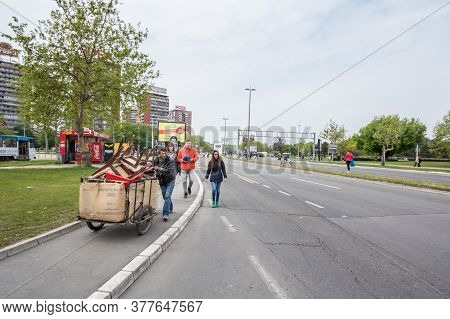 Belgrade, Serbia - April 22, 2017: Young Man From The Roma Community Pulling A Cart To Collect Garba