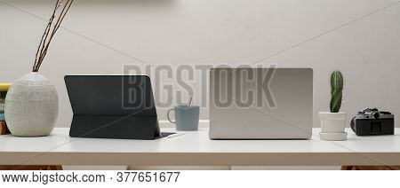 Home Office Desk With Digital Devices, Camera, Mug And Decorations