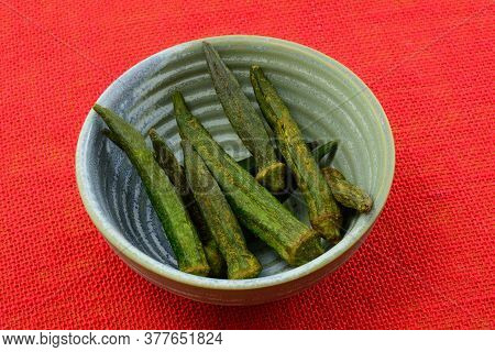 Soy Sauce Sesame Flavored Dried Okra Chips In Ceramic Snack Bowl On Red Tablecloth