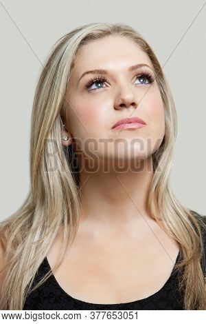 Contemplative young woman looking up over gray background