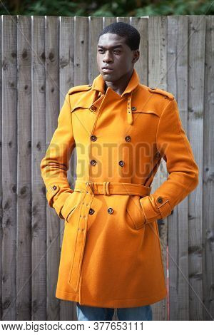 Young African American man in orange trench coat standing with hands in pockets