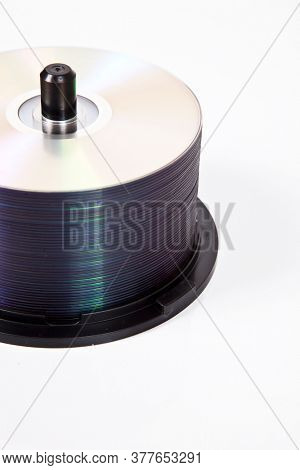 Stack of compact discs on a spindle over white background