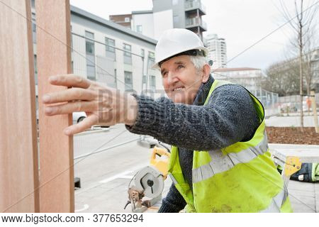 Happy senior male worker at working at construction site