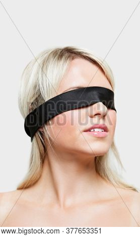 Young woman blindfolded over gray background