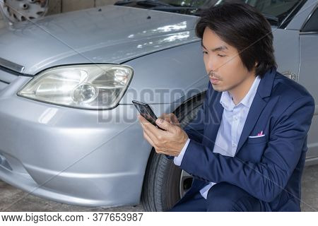 Asian Insurance Agent Or Insurance Agency In Suit See Smartphone And Inspecting Car Crash From Accid