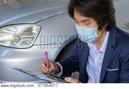 Asian Insurance Agent Or Insurance Agency In Suit Wear Mask Writing Car Crash Report And Inspecting