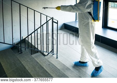 Sanitizing Worker Cleaning Up The Staircase At The Shopping Mall With An Antiseptic To Prevent Covid