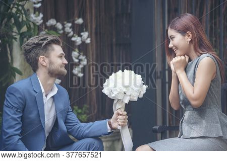 Caucasian Handsome Man Giving Flowers To Asian Girlfriend Asking For Proposing To Marry Him At Green