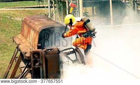 Firefighter Fighting With Flame Using Fire Hose Chemical Water Foam Spray Engine. Fireman Wear Hard