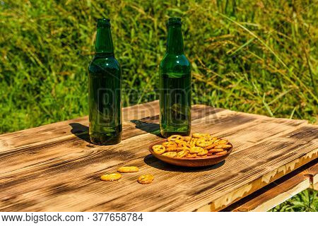 Two Bottle Of Beer And Ceramic Plate With Salted Pretzels On Rustic Wooden Table