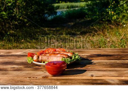 Ceramic Plate With Grilled Sausages, Sliced Tomatoes And Lettuce Leaves On Rustic Wooden Table