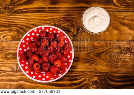 Ceramic Plate With Ripe Raspberries And Sour Cream On Rustic Wooden Table. Top View