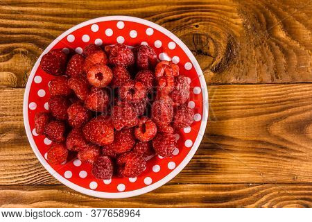 Ceramic Plate With Ripe Raspberries On Rustic Wooden Table. Top View