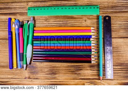 Different School Stationeries (pens, Pencils And Ruler) On Wooden Background. Top View