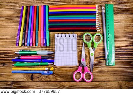 Different School Stationeries (pens, Notepad, Pencils, Felt Tip Pens, Scissors And Ruler) On Wooden