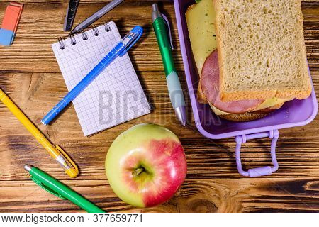Ripe Apple, Different Stationeries And Lunch Box With Sandwiches On Wooden Table. Top View