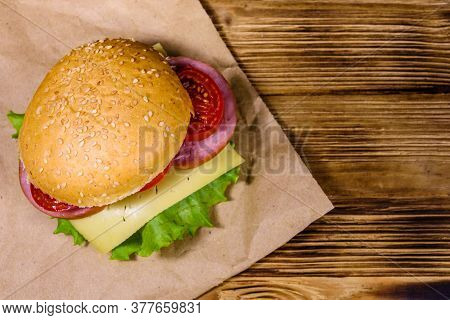 Fresh Hamburger On Brown Paper On Rustic Wooden Table