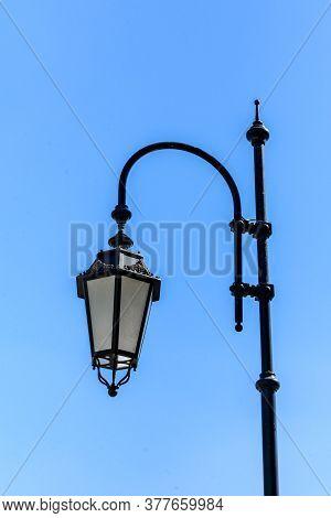 Old Lantern On Metal Post Against Blue Sky