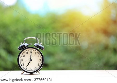 Vintage Alarm Clock On Wooden Desk With Green Nature And Sunlight Background