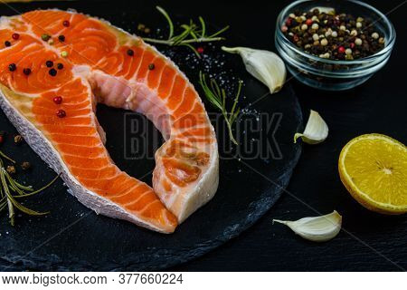 Raw Salmon Steak And Spices On Slate Board