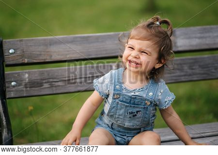 Adorable Little Girl Laughing. Beautiful Female Kid In Denim Sitting On The Bench In Park. Happy Lit